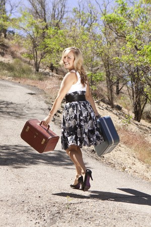 Girl walking down road carrying suitcases and looking back over her shoulder.