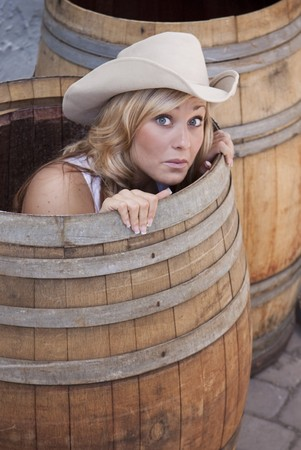 Young cowgirl peeking out of a barrel with a worried look on her face.