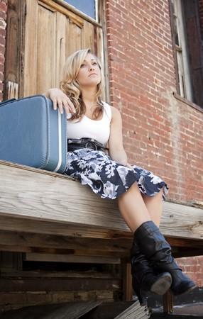 Portret van een tiener meisje, zittend op de stappen van een vervallen gebouw met haar koffer naast haar en een droevige uitdrukking op haar gezicht.