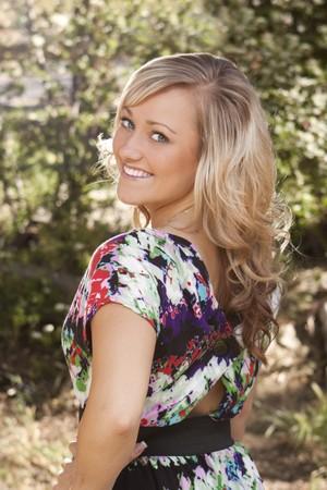 Portret van een mooie jonge vrouw die over haar schouder kijken. Buiten, is met bomen en land-omgeving ingesteld.  Stockfoto