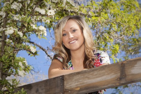 Young girl in an outdoor setting with a flowering tree and a wooden fence.