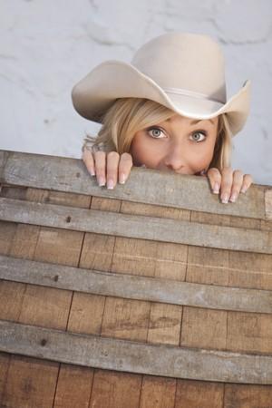 Jonge cowgirl gluren uit een vat met een humoristische uitdrukking op haar gezicht.  Stockfoto