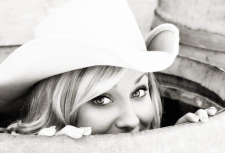 Jonge cowgirl gluren uit een vat met een glimlach op haar gezicht.  Stockfoto
