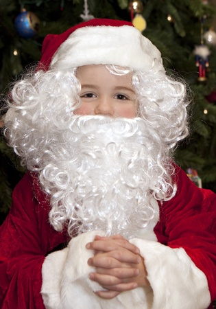 Young boy in front of Christmas tree wearing a Santa Claus suit.