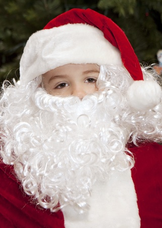 Thoughtful boy dressed as Santa Claus with a Christmas Tree backdrop.