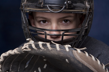 Young teenage boy in catchers mask with glove ready and dramatic dark blue background. Stock Photo