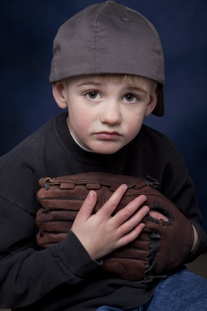 Young boy with a baseball hat and glove and a sad expression.