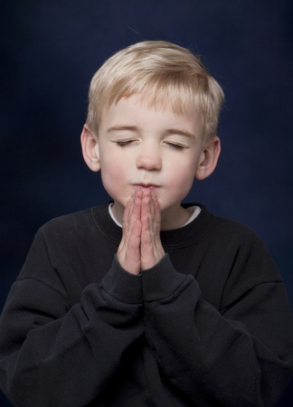 Jonge blonde jongen met zijn handen samen in gebed. Stockfoto