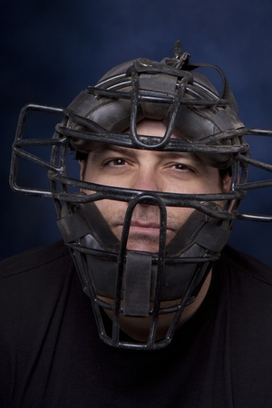 Dertig-iets man in een catcher masker met een dramatische blauwe achtergrond.