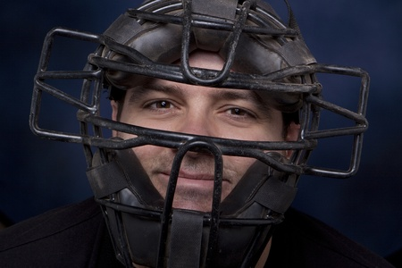 Thirty-something man in a catcher's mask with a dramatic blue background. Stock Photo - 8754698