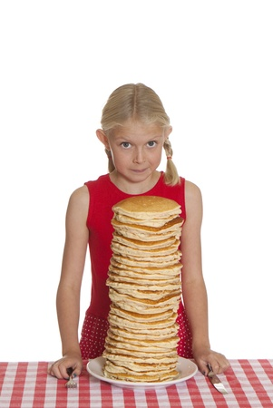 flapjacks: Little girl with a giant plate of pancakes, a knife and fork on a table cloth.