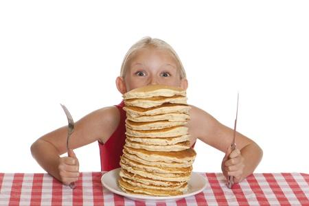 Meisje gluren over een gigantische plaat van pannenkoeken, een vork en mes in haar handen.