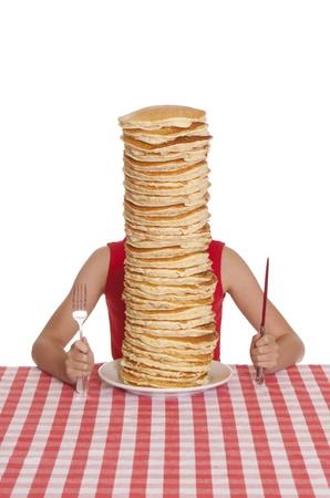 Klein meisje met een gigantische plaat van pannenkoeken, een mes en vork op tafel doek. Stockfoto