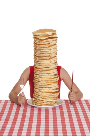 hotcakes: Little girl with a giant plate of pancakes, a knife and fork on a table cloth.