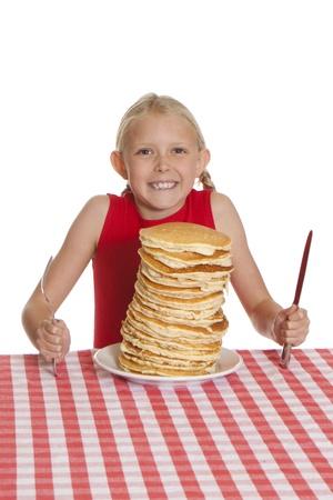 Klein meisje met een gigantische plaat van pannenkoeken, een mes en vork op tafel doek. Ondiepe DOF met focus op de pannenkoeken.
