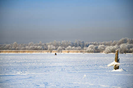 frostily: Winter pazza, a fisherman on the ice of a frozen river
