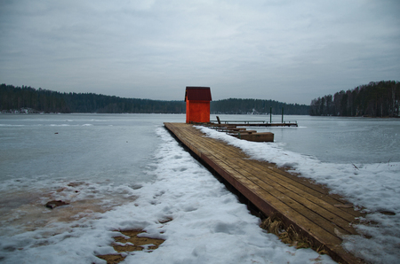 filming point of view: red house on pier winter landscape of the shoreline of the lake with a dock