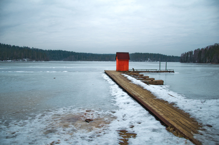the bigger picture: red house on pier winter landscape of the shoreline of the lake with a dock