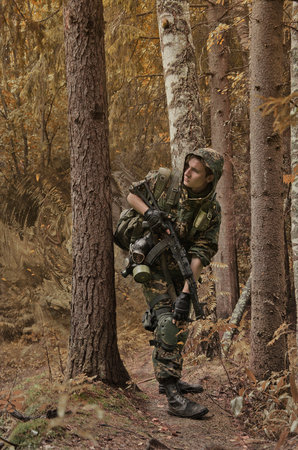 militant: soldiers in forest, thematic shooting war and Stalker Stock Photo