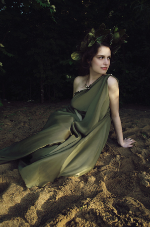 allusion: woman in a wreath of leaves, woman portrait, an allusion to Greco-Roman mythology, the image of the nymph. Stock Photo