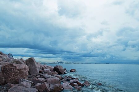 storm tide: city on horizon, storm clouds over a seaside town, rocky shore