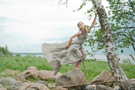 allusion: woman in wind, by the sea, gown of silver parachute silk necklace of shells and pearl gold jewelry. Wind storm. An allusion to the Scandinavian and Celtic mythology.