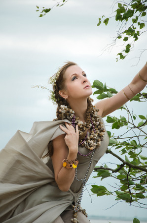 scandinavian girl: girl with flowers in her hair, gown of silver parachute silk necklace of shells and pearl gold jewelry. Wind storm. An allusion to the Scandinavian and Celtic mythology.