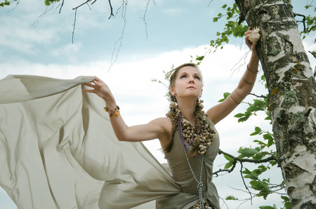 thin shell: girl into wind, gown of silver parachute silk necklace of shells and pearl gold jewelry. Wind storm. An allusion to the Scandinavian and Celtic mythology.