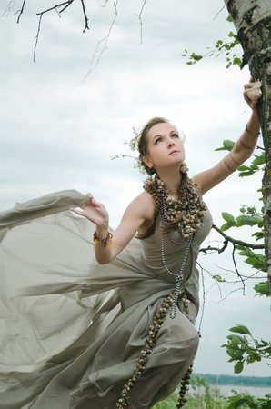 allusion: girl into wind with flowers in her hair, gown of silver parachute silk necklace of shells and pearl gold jewelry. Wind storm. An allusion to the Scandinavian and Celtic mythology.