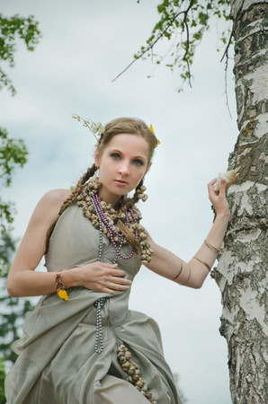 girl near a tree, gown of silver parachute silk necklace of shells and pearl gold jewelry. Wind storm. Flowers in the hair An allusion to the Scandinavian and Celtic mythology. Stock Photo