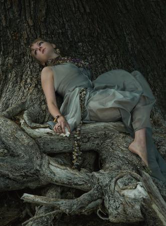 vrouw en boom, in een jurk van zijde en oude boom. Sieraden gemaakt van schelpen van zeeslakken en schelpen.