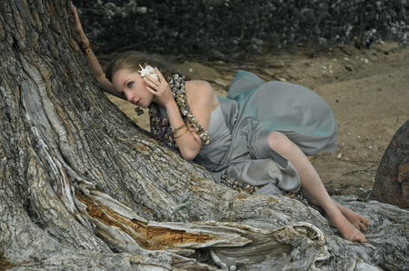 thin shell: young woman listening to the sound of the sea in a seashell sitting on a tree