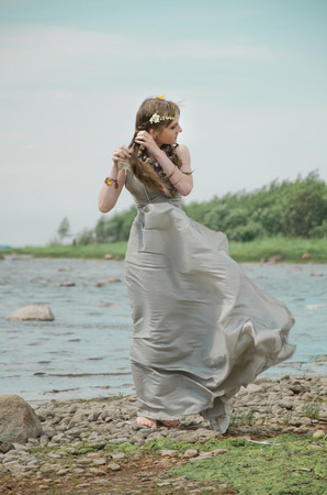 woman unwinding spit, gown of silver parachute silk necklace of shells and pearl gold jewelry. Wind storm. An allusion to the Scandinavian and Celtic mythology.