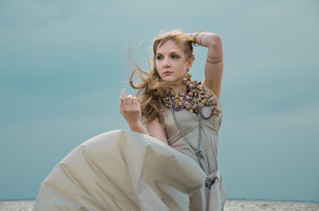 adult mermaid: mermaid in sea, gown of silver parachute silk necklace of shells and pearl gold jewelry. Wind storm. An allusion to the Scandinavian and Celtic mythology.