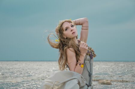 mermaid in sea, gown of silver parachute silk necklace of shells and pearl gold jewelry. Wind storm. An allusion to the Scandinavian and Celtic mythology.