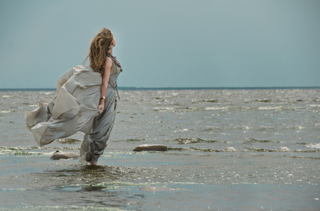 saltwater pearl: girl by sea, gown of silver parachute silk necklace of shells and pearl gold jewelry. Wind storm. An allusion to the Scandinavian and Celtic mythology.