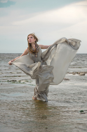 woman by sea, gown of silver parachute silk necklace of shells and pearl gold jewelry. Wind storm. An allusion to the Scandinavian and Celtic mythology.