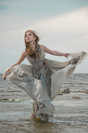 allusion: woman by sea, gown of silver parachute silk necklace of shells and pearl gold jewelry. Wind storm. An allusion to the Scandinavian and Celtic mythology.
