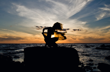 silhouette against the sunset, woman on the beach Stock Photo