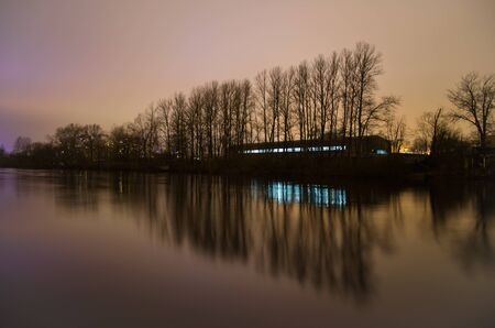 oxbow: city outskirts and water, geometric perspective of the trees reflected in the water surface