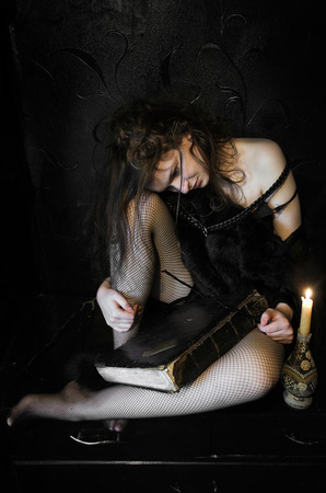 young woman casts a spell with candles in a dark room