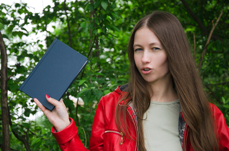 girl in a red jacket with a blue book in his hands Stock Photo