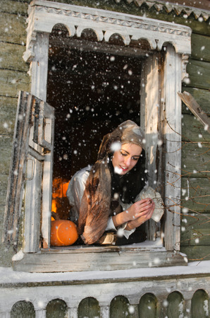 Gypsy woman with cards laughs looking out of the window under the snow