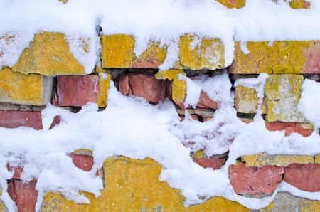 old crumbling brick walls covered with snow
