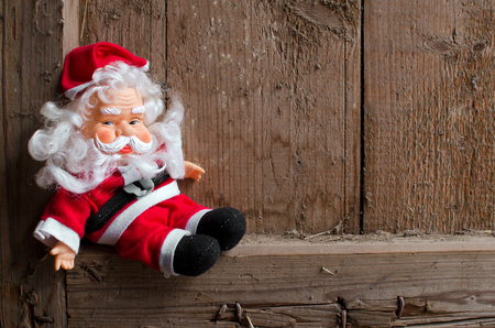Toy Santa Claus on vintage wooden background
