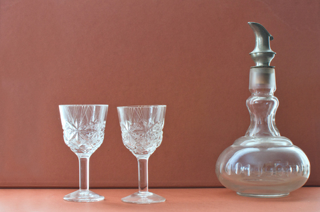 decanter with steel lid and two glasses on a vintage background