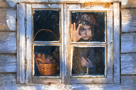 witch stares out the window with anticipation she even leaned a hand to the frame, the window is clearly something interesting Stock Photo