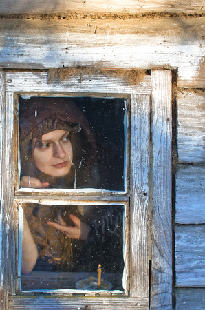 beautiful peasant woman wrapped in a woolen shawl with an insidious smile looks out into the window of the house, something she was interested in