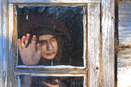this woman is clearly very sad, she looks out the window, stroking the glass and waits for someone can be a will never come Stok Fotoğraf