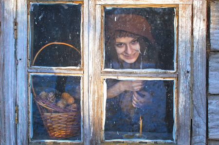 vile grinning young witch looking out the window of his house on a winter day, it was warm and cozy, especially since it was wrapped in a woolen shawl, and the window frosty and cold, everything froze
